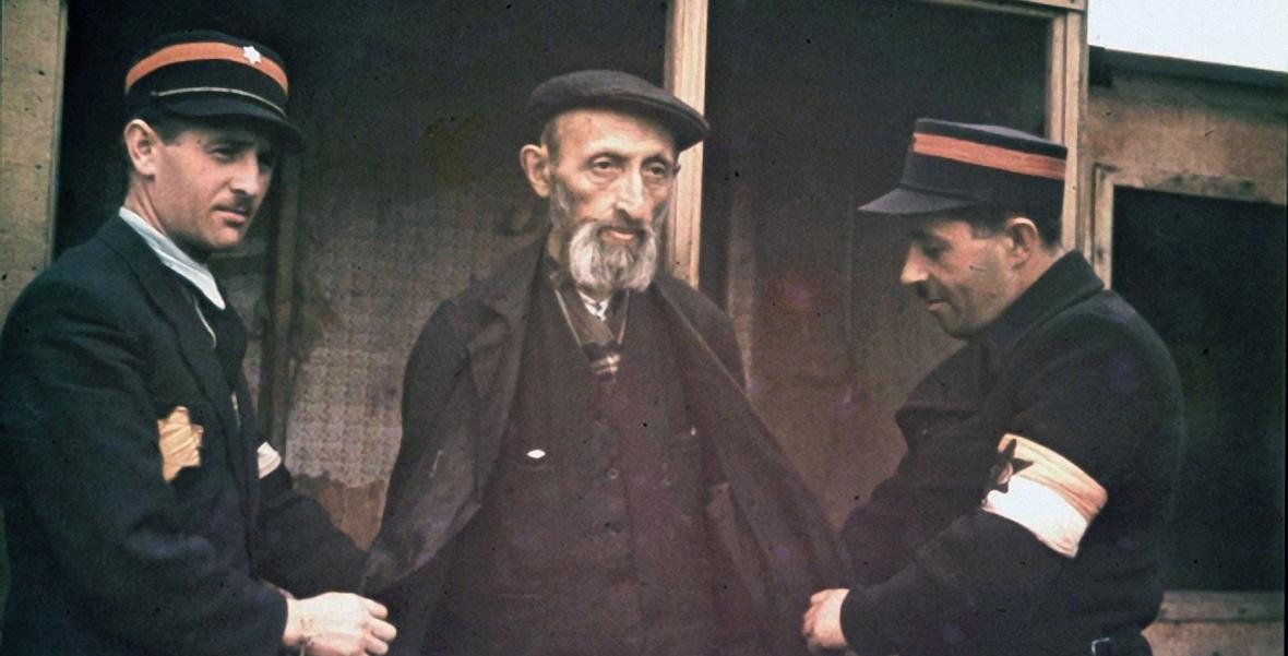 Stary Żyd wyprowadzany przez żydowskich policjantów podczas Wielkiej Szpery
