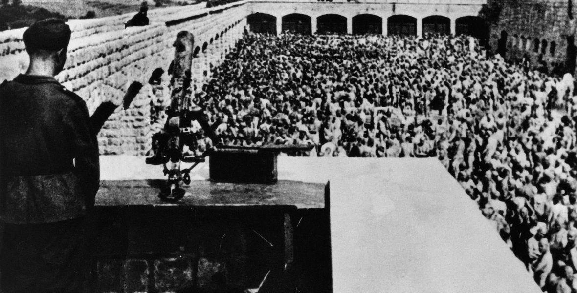 Strażnik obserwuje więźniów obozu koncentracyjnego Mauthausen-Gusen czekających nago na apel. Lata 40. XX wieku