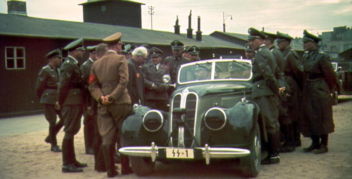 Reichsführer SS Heinrich Himmler (na siedzeniu pasażera) wizytuje łódzkie getto. Z przodu po lewej (odwrócony tyłem) stoi Werner Ventzki. Przed nim z siwymi włosami Chaim Mordechaj Rumkowski
