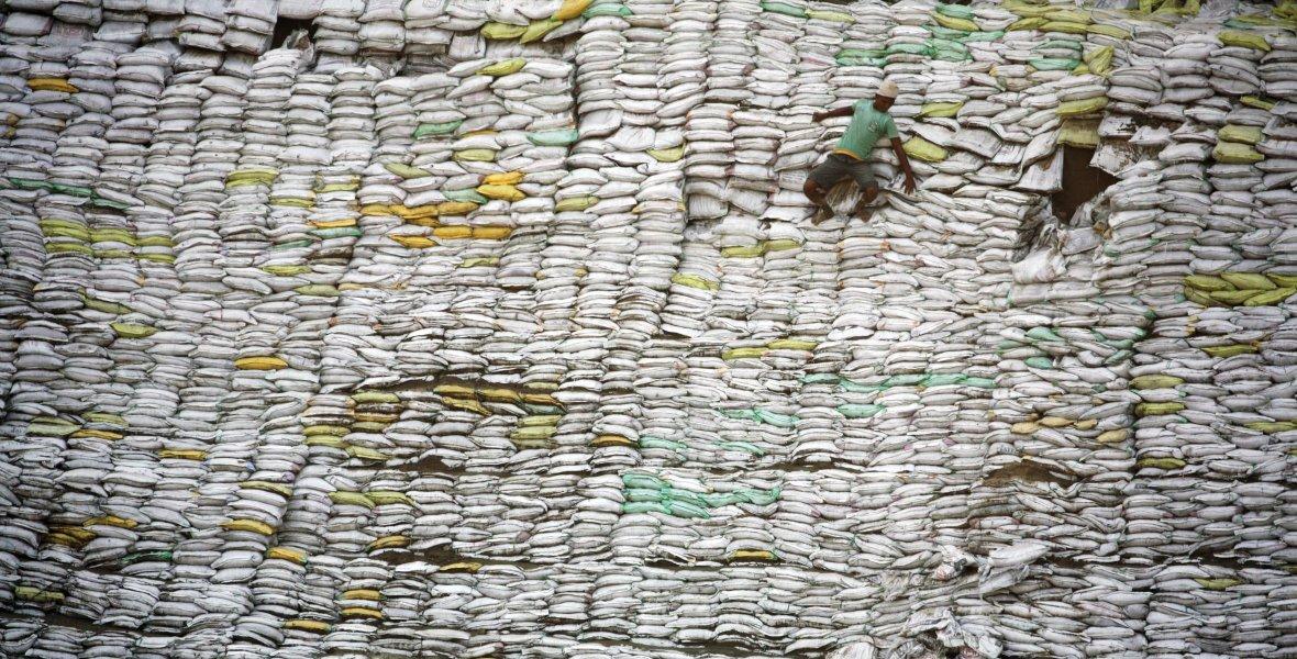 Budowa w New Dehli. Robotnik schodzi ze sterty worków z piaskiem