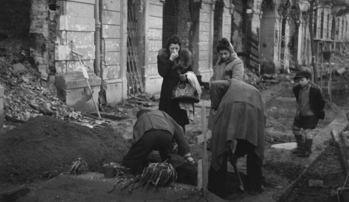 Warszawa 1945. Ulica Wspólna, ekshumacja ciał ofiar działań wojennych. Dokładny miesiąc i dzień wydarzenia nieustalone