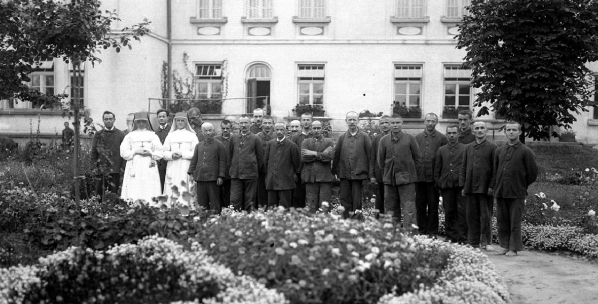 Grupa pacjentów z siostrami zakonnymi - pielęgniarkami w szpitalnym ogrodzie. Sierpień 1927