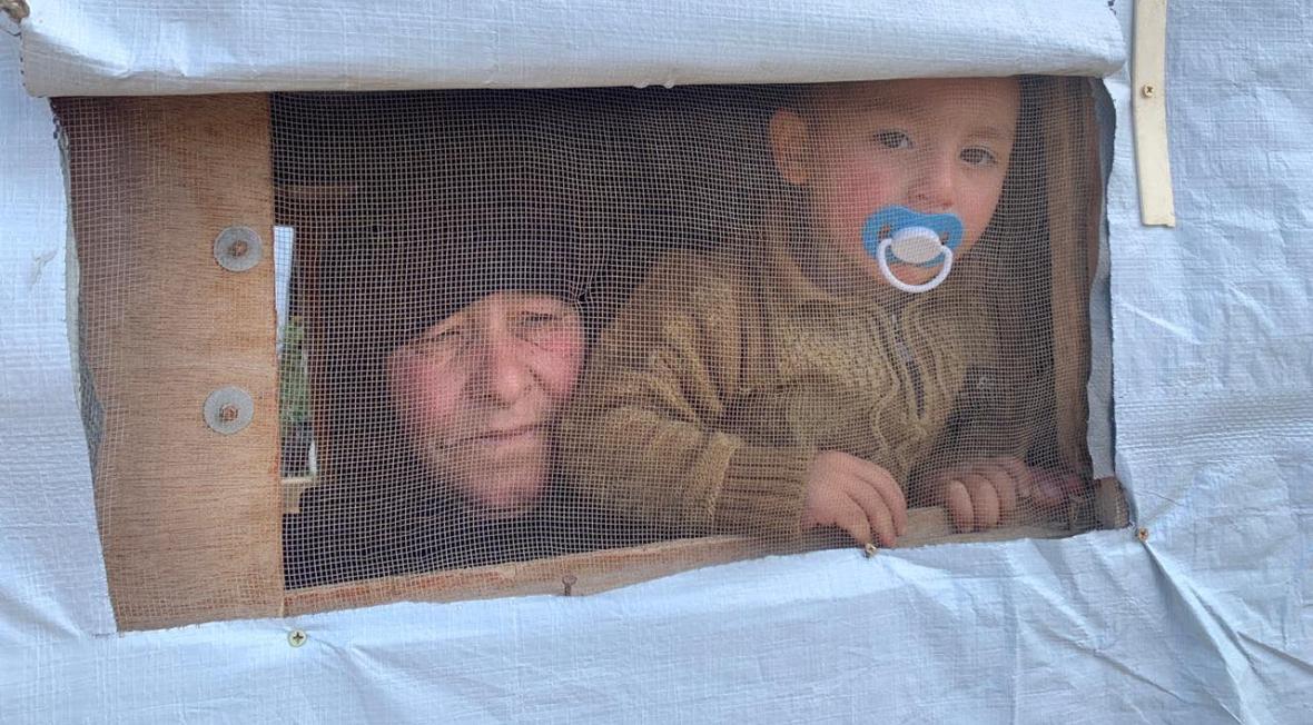 Kobieta z dzieckiem wygląda przez prowizoryczne okienko swojego prowizorycznego domu w obozie dla uchodźców w Arsalu