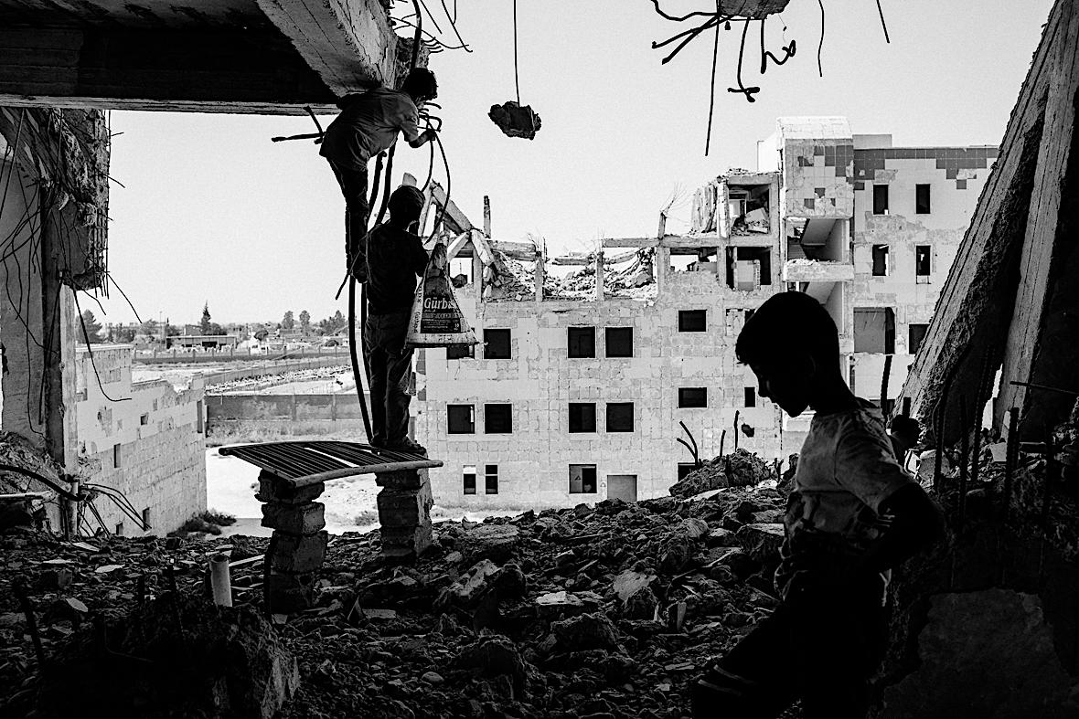 Chłopcy wycinają fragmenty zbrojenia ze zbombardowanego budynku w Ar-Rakka