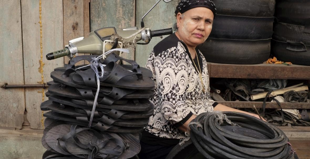 Sprzedawczyni klapek z recyklingowanych opon na bazarze Mann Thiri w Mandalaju w Mjanmie (Birma)