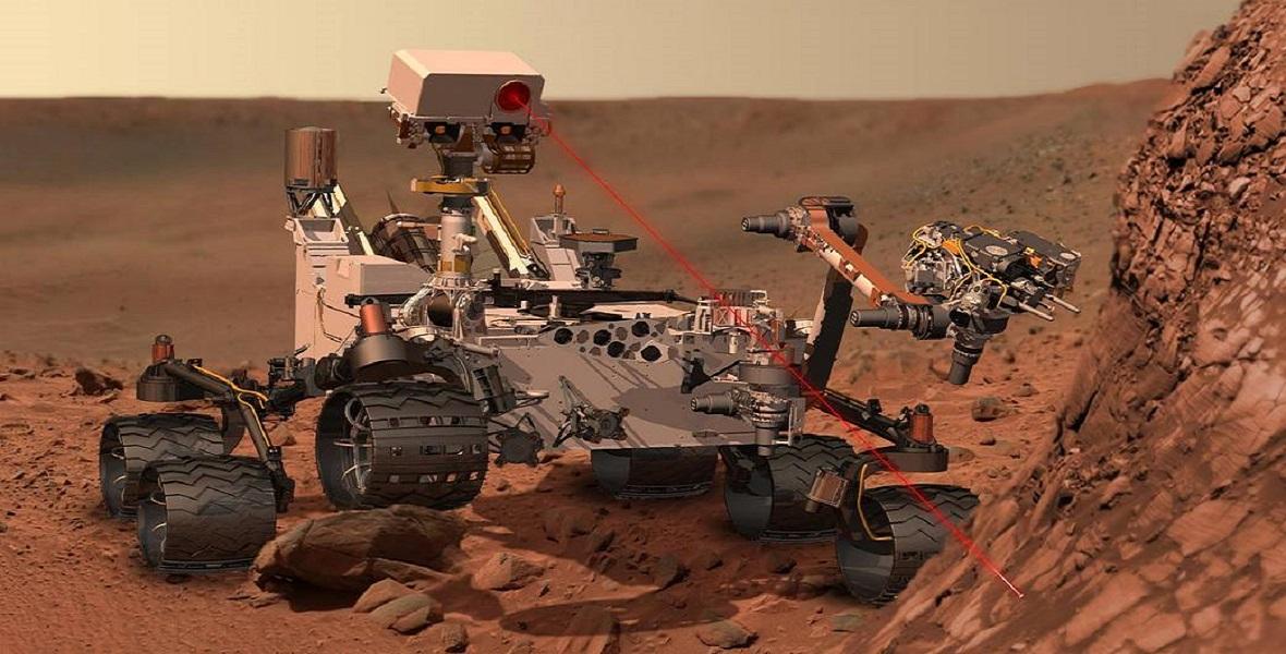Łazik Curiosity na Marsie. W rzeczywistości laser nie jest widocznym, ale dla celów ilustracyjnych pokazano go jako widoczne czerwone światło.